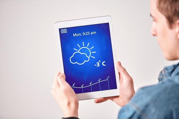 흰 벽에 태블릿 앱에서 일기 예보를 확인하는 젊은 남자의 어깨보기 이상