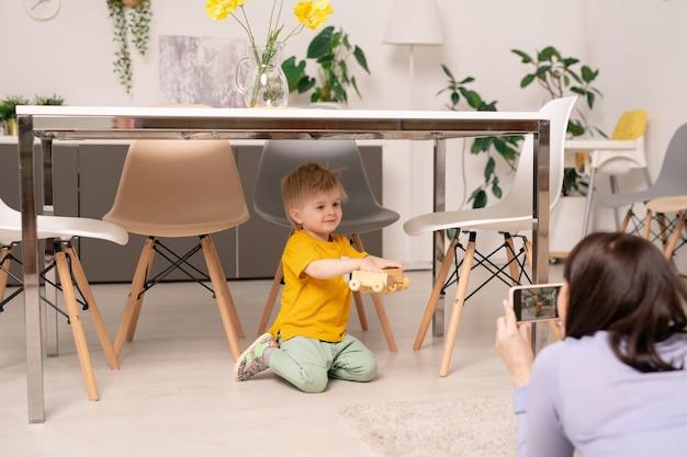 부엌 테이블 아래에 앉아 장난감으로 아기 아들을 촬영하는 젊은 어머니의 어깨보기 이상