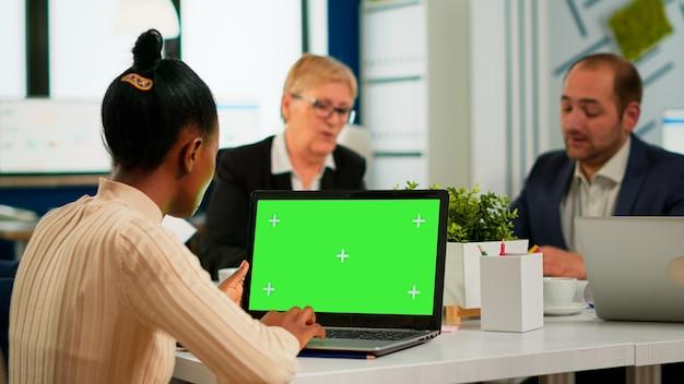多様なチームが働いている間、緑色の画面でラップトップを見ている会議デスクに座っているアフリカのマネージャーの女性の肩越しに。クロマキーディスプレイでプロジェクトを計画している多民族の人々