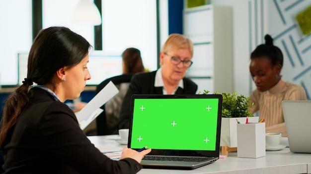 다양한 팀이 백그라운드에서 작업하는 동안 녹색 화면 모형이 있는 노트북을 보고 회의 데스크에 앉아 있는 관리자의 지지자 위에. 크로마 키 디스플레이에 대한 다민족 사람들 계획 프로젝트