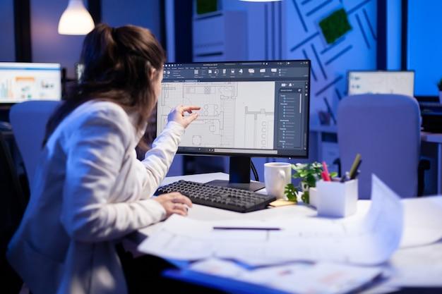 건축 계획을 그리고 데스크탑 컴퓨터에서 cad 소프트웨어를 보고 있는 엔지니어 여성의 어깨 너머로