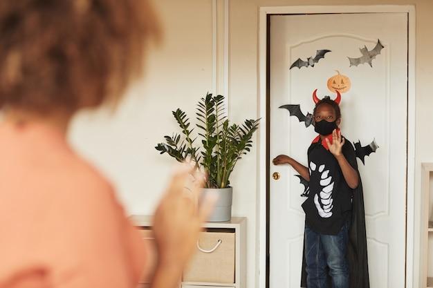 악마 할로윈 의상을 입고 친구들과 속임수를 쓰러 나가는 어린 아들을 배웅하는 젊은 어머니의 어깨 너머 샷.