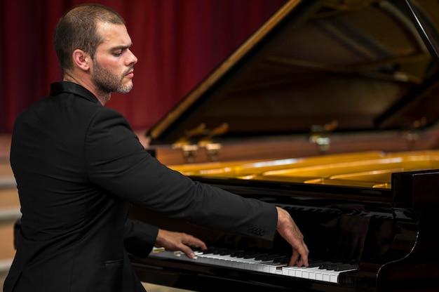 肩越しにピアノを弾く男