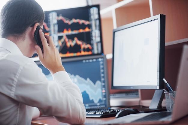 전화로 주문을 받으면서 온라인으로 증권 중개인 거래를 어깨 너머로 볼 수 있습니다. 백그라운드에서 차트 및 데이터 분석으로 가득 찬 여러 컴퓨터 화면.