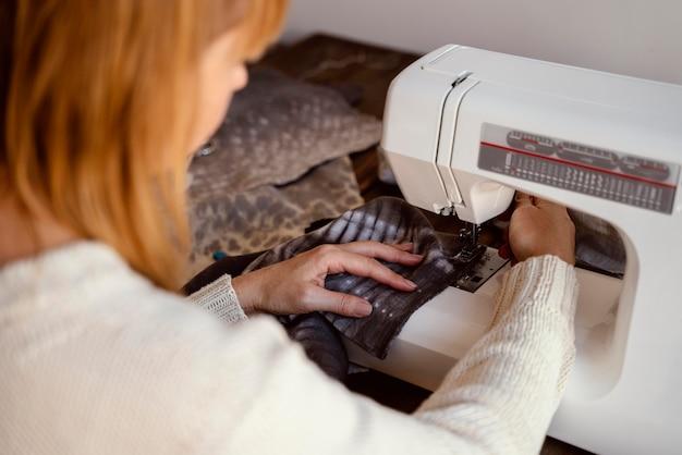 Женщина-портной через плечо с помощью швейной машины