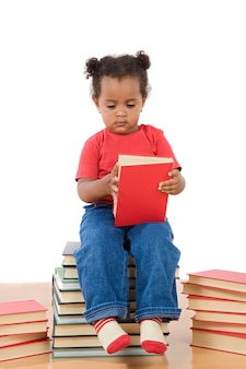 Over white background上の本の山に座って読書する愛らしいアフリカの赤ちゃん