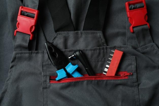 전체 배경에 작업 도구가있는 작업복을 닫습니다.