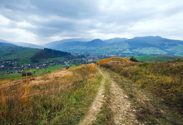 村と田舎道(カルパティア山脈、ウクライナ)のある曇りの秋の山の風景。