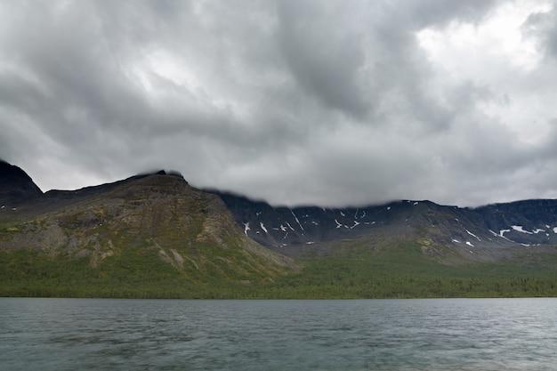 Пасмурное облачное небо над озером и горами хибины.