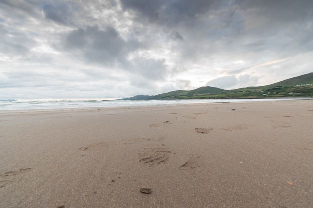 Overcast sky over sands of a beach with tide out. mauntains in the distance.