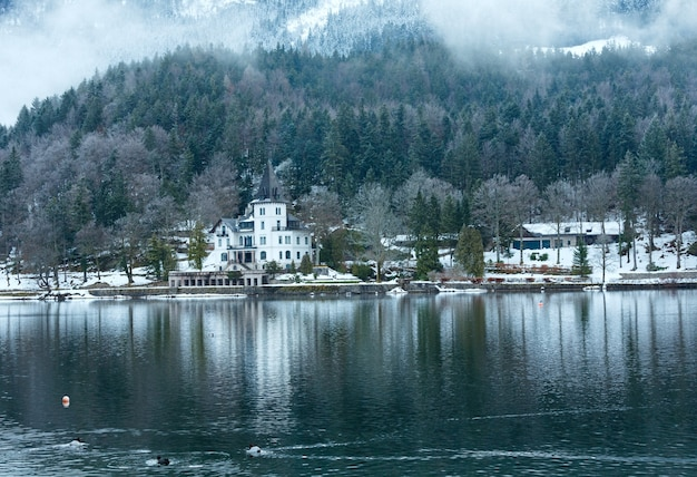 Пасмурная зима, вид на альпийское озеро грундльзее с белым домом (австрия)