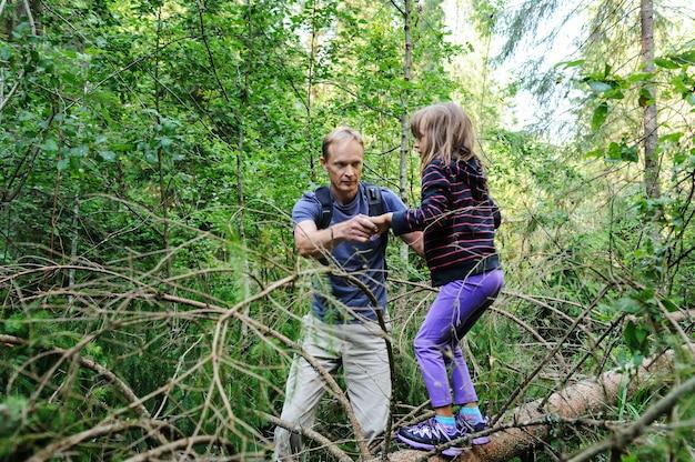 Преодоление препятствий во время прогулки по лесу. взрослый помогает девочке пересечь упавшее дерево.