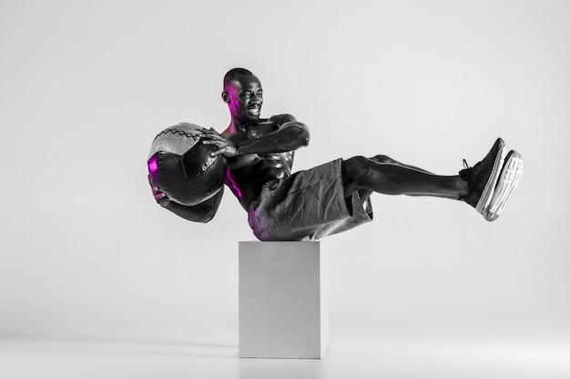 극복. 회색 스튜디오 배경 위에 젊은 아프리카 계 미국인 보디 빌딩 훈련. 공을 sportwear에 근육질의 단일 남성 모델. 스포츠, 보디 빌딩, 건강한 라이프 스타일의 개념.