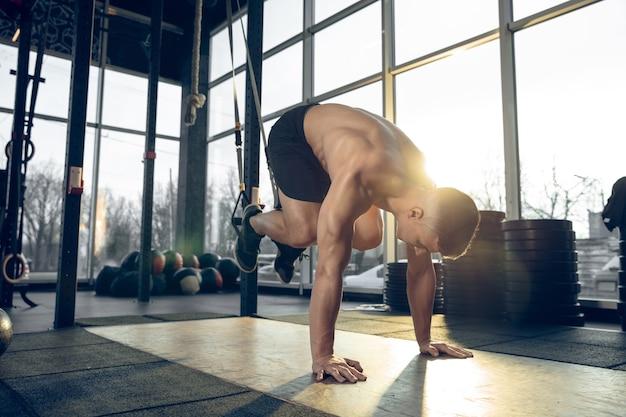 극복. 젊은 근육질의 백인 운동선수는 체육관에서 훈련하고, 근력 운동을 하고, 연습하고, 웨이트 링으로 상체를 운동합니다. 피트니스, 웰빙, 스포츠, 건강한 라이프 스타일 개념.