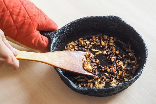 Переваренный лук на сковороде. плохая кухня. понятие о вредной пище и канцерогенных веществах.