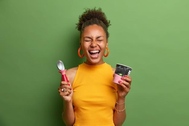 과감한 쾌활한 어두운 피부의 십대 소녀가 큰 소리로 웃고, 재미 있고, 맛있는 냉동 디저트를 먹고, 아이스크림 컵과 숟가락을 들고 밝은 노란색 옷을 입고 행복을 표현합니다.