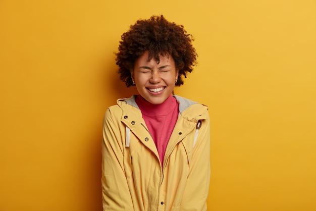 과감한 쾌활한 여성은 눈을 감고 넓게 미소 지으며 성공적인 하루 후 매우 행복하며 뛰어난 이벤트를 기다릴 수 없으며 윈드 브레이커를 착용합니다.