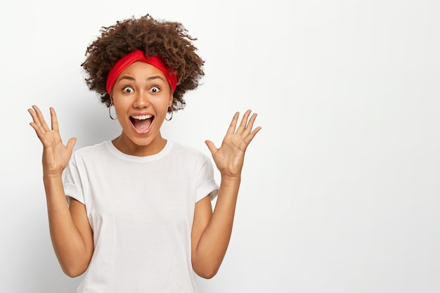 Overemotive dark skinned woman raises palms, keeps mouth widely opened, reacts on something awesome, dresed in casual wear