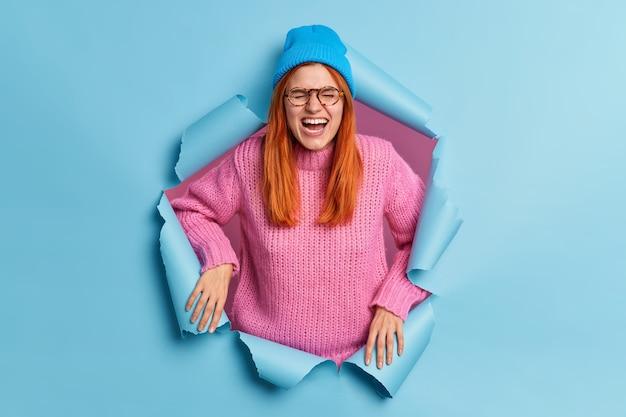 과감한 생강 젊은 유럽 여성이 즐겁게 미소 짓고 캐주얼 한 옷을 입고 행복을 외치며 종이 찢어진 구멍에 실내 안경 스탠드를 착용합니다.