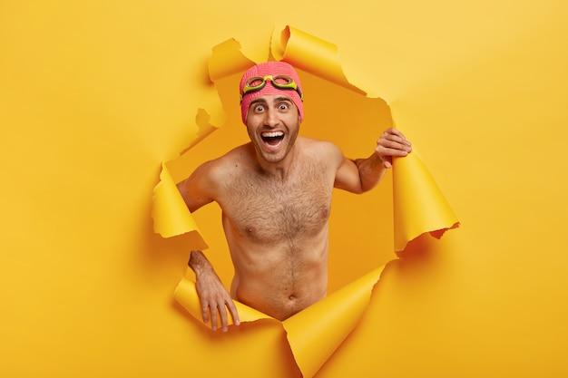 과감한 남자 수영 선수는 셔츠가없는 포즈, 수영복과 고글 착용, 찢어진 종이 구멍에서 포즈를 취하고 행복하게 웃는다.