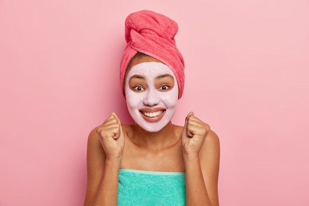 Overemotive woman supples facial skin, raises clenched fists, looks positively at camera, wears wrapped towel on head and body