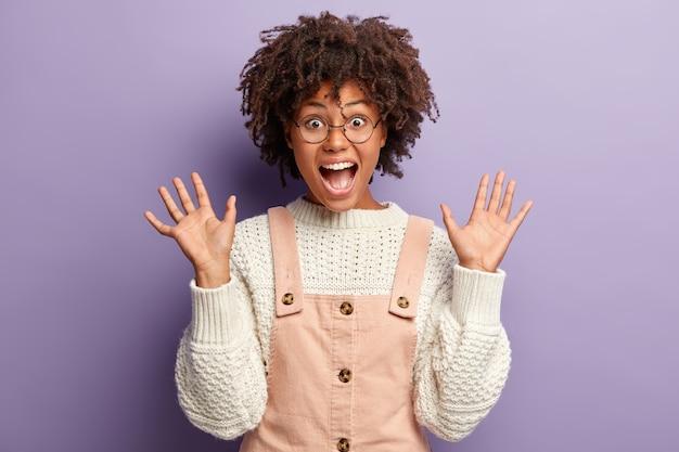 Giovani gesti femminili ipermotivi attivamente mentre condivide impressioni positive, grida di gioia, mostra i palmi delle mani, vestiti con tute alla moda, indossa occhiali rotondi, isolati su un muro viola. wow fico