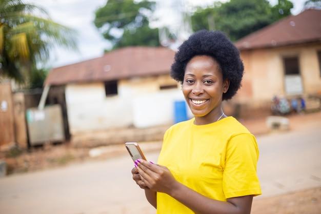 스마트폰으로 소셜 미디어를 확인하고 온라인 쇼핑을 하는 과도하게 흥분한 아프리카계 미국인 여성