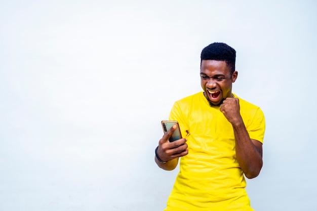 온라인에서 친구들과 채팅하는 좋은 소식을 받은 후 축하하는 과도하게 흥분한 젊은 흑인 남성 힙스터
