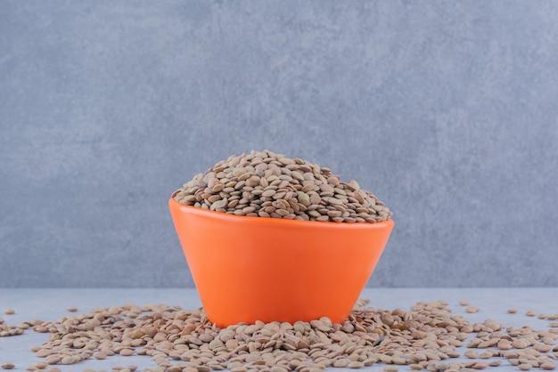 대리석 표면에 흩어져 있는 갈색 렌즈콩 더미에 가득 찬 그릇