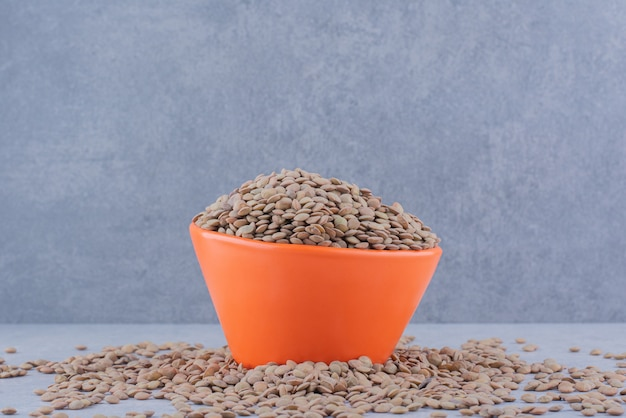 Overfilled bowl nested in a scattered pile of brown lentil on marble surface