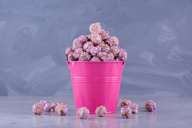 Overfilled bucket with flavored popcorn fallen out on marble background. high quality photo
