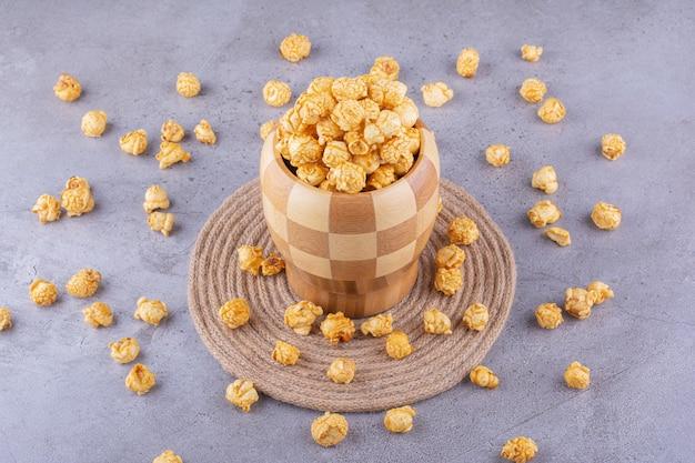 Переполненная клетчатая миска, окруженная рассыпанным карамельным попкорном на мраморном фоне. фото высокого качества
