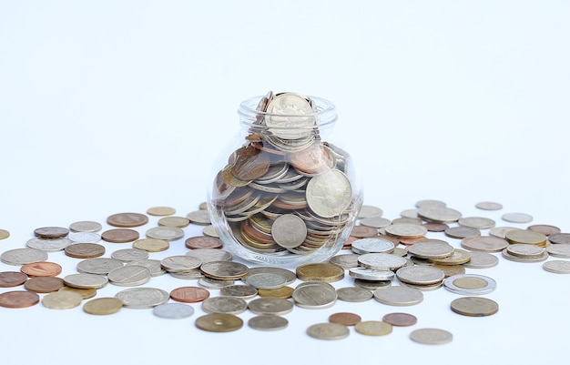 Overflowing jar of international coins on white background