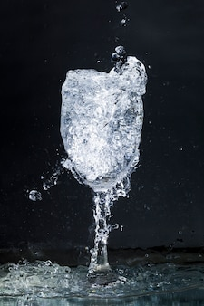 Overflowing water glass on dark background