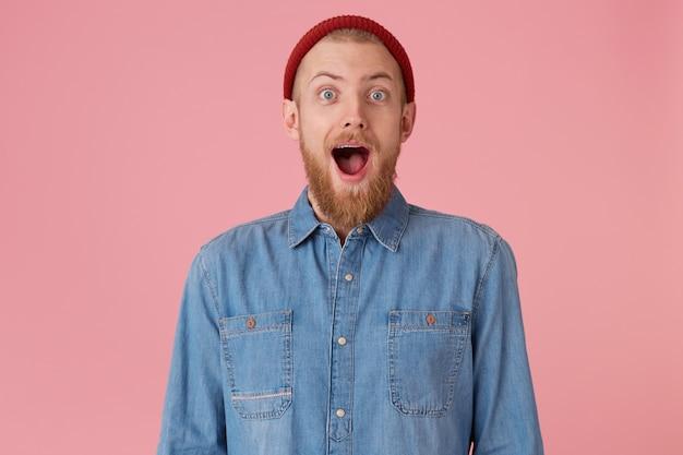 赤い厚いあごひげを生やした赤い帽子をかぶった前向きな感情で溢れている嬉しい男は、興奮して口を大きく開き、顎を落とし、ピンクの壁に隔離されています