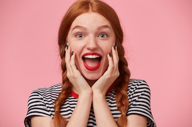Overflowing with positive emotions joyful red-haired girl with two braids keeps hands near her face and openes mouth widely in excitement, with red lips, white healthy teeth, isolated on pink wall