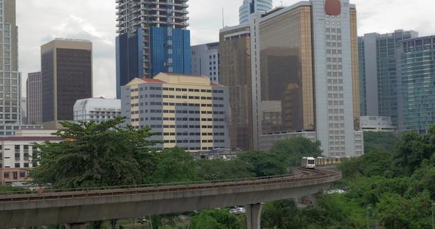 Надземные поезда движутся через куала-лумпур на фоне городского пейзажа с высотной архитектурой, малайзия