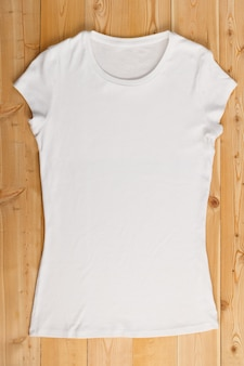 Overhaed view of female t-shirt on a natural wooden background