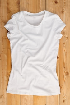 Overhaed view of white t-shirt on a natural wooden background