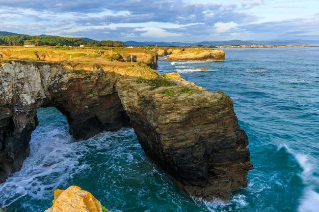 Свисающие скалы над пляжем соборов во время прилива кантабрикское побережье испании