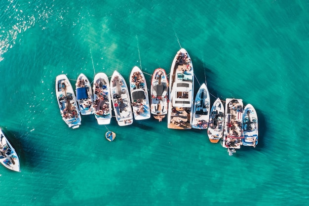 Overhead aerial drone shot of different sized boats docked close to each other near the pier