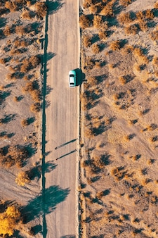 Overhead aerial drone shot of a narrow desert road with a car on the side of the road