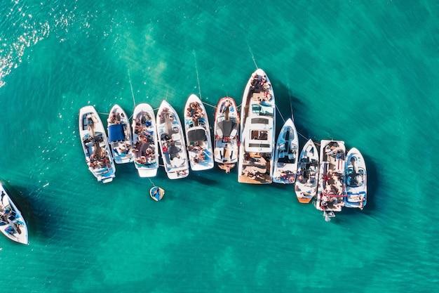 桟橋の近くで互いに近接してドッキングされたさまざまなサイズのボートのオーバーヘッド空中ドローンショット