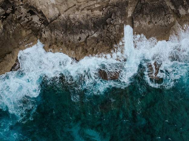 Overhead aerial shot of the beautiful ocean cliffs and the water splashing on them