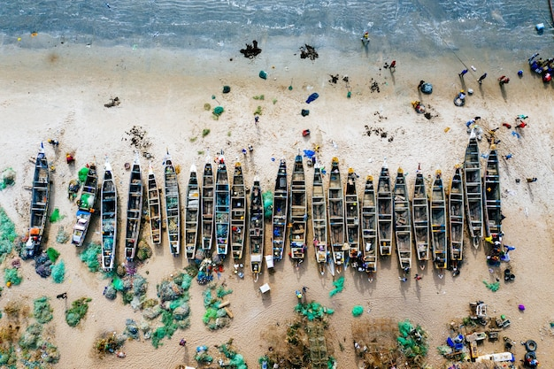 Overhead aerial shot of different colored boats on a sandy beach with the sea nearby