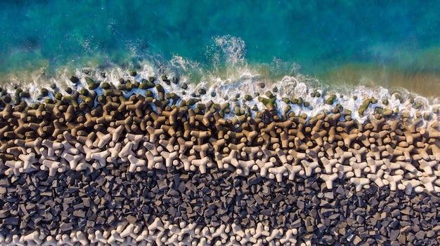 岩に対する波状の青い海の頭上空中ショット
