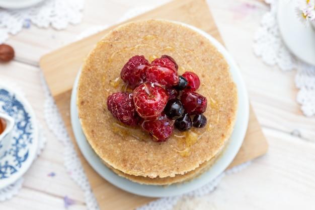 꿀과 딸기와 함께 원시 채식주의 팬케이크의 오버 헤드 근접 촬영 샷