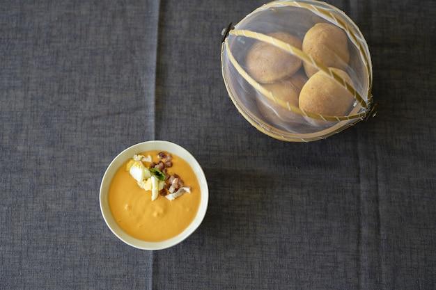 Colpo ambientale del primo piano di una salsa di zuppa all'arancia in una ciotola bianca con il pane su una tovaglia nera