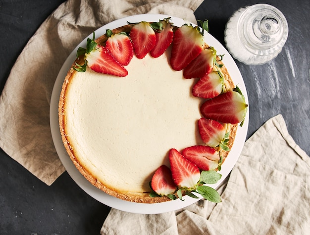 Overhead closeup shot of a strawberry cheesecake on a white plate