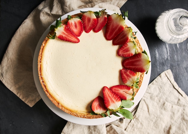 Overhead closeup shot of a strawberry cheesecake on white plate